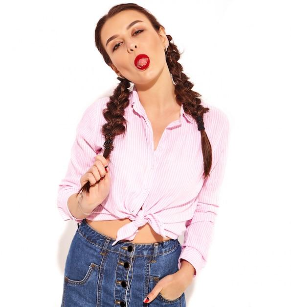 Portret van jong gelukkig het glimlachen vrouwenmodel met heldere make-up en rode lippen met twee geïsoleerde vlechten in zomer kleurrijk roze gebonden overhemd, die haar tong tonen Gratis Foto