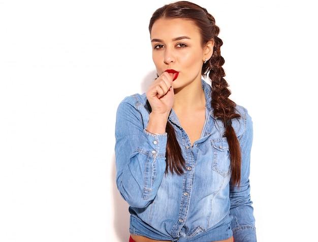 Portret van jong gelukkig het glimlachen vrouwenmodel met heldere make-up en rode lippen met twee vlechten in geïsoleerde de kleren van de de zomerjeans. bijtende vinger Gratis Foto
