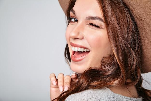 Portret van jong modieus het lachen model in grijze toevallige de zomerkleren in bruine hoed met natuurlijke make-up Gratis Foto
