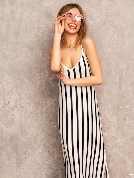 Portret van jong mooi glimlachend meisje in trendy de zomer gestreepte kleding. het sexy onbezorgde vrouw stellen. positief model dat pret in ronde zonnebril heeft. knipogend Gratis Foto