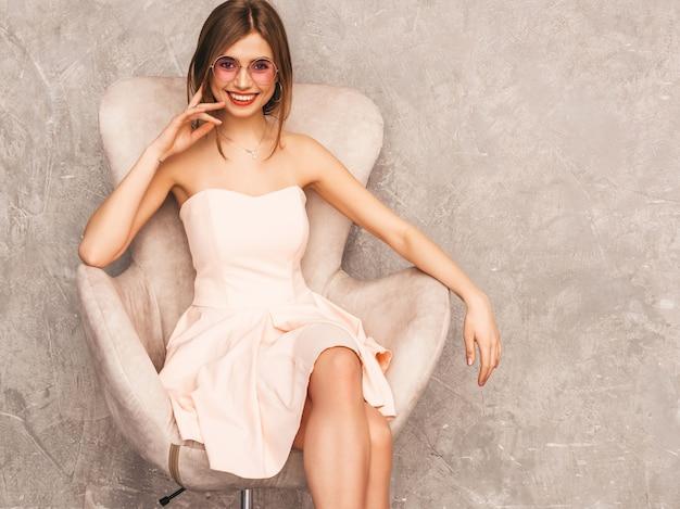 Portret van jong mooi glimlachend meisje in trendy de zomer lichtrose kleding. sexy zorgeloze vrouw zittend op beige stoel. poseren in luxe interieur Gratis Foto