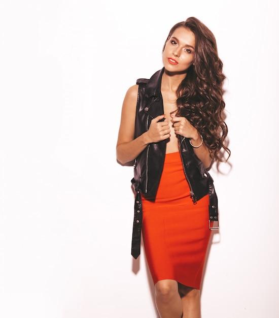 Portret van jong mooi hipstermeisje in trendy de zomer rode rok en zwart leerjasje. sexy onbezorgde die vrouw op wit wordt geïsoleerd. brunette model met make-up en kapsel Gratis Foto