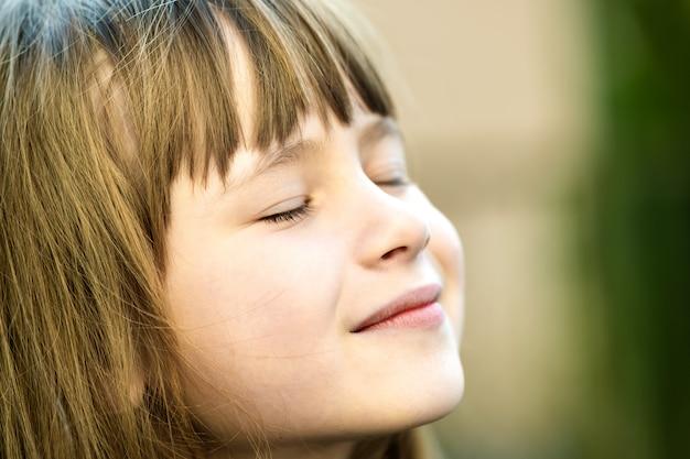 Portret van jong mooi kindmeisje dat met lang haar in openlucht van warme zonnige dag in de zomer geniet. schattige vrouwelijke jongen ontspannen op frisse lucht buiten. Premium Foto