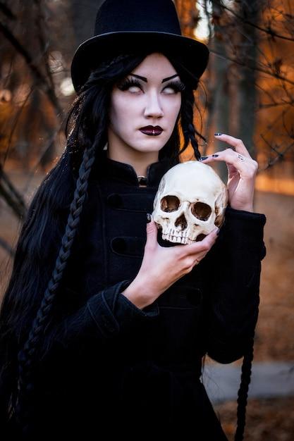 Portret van jong mooi meisje met donkere make-up op haar gezicht en skelet in handen Premium Foto