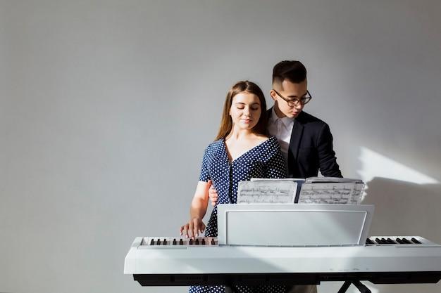 Portret van jong paar die de piano samen tegen grijze muur spelen Gratis Foto
