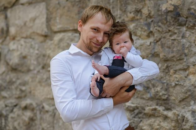 Portret van jong schreeuwend de babymeisje van de vaderholding over witte bakstenen muur Premium Foto