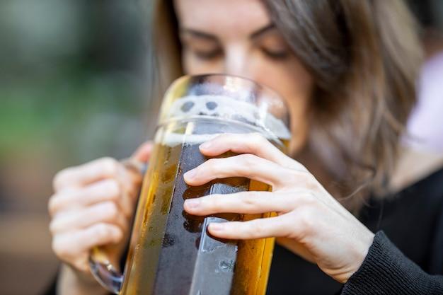 Portret van jong vrouw het drinken bier bij de bar Premium Foto