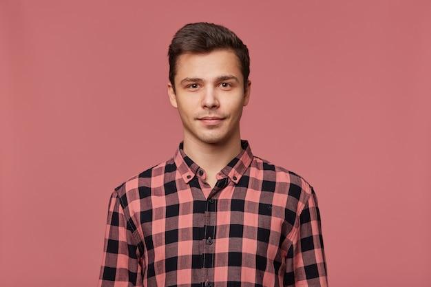 Portret van jonge aantrekkelijke man in geruit hemd, kijkt rustig naar de camera, staat op roze achtergrond. Gratis Foto