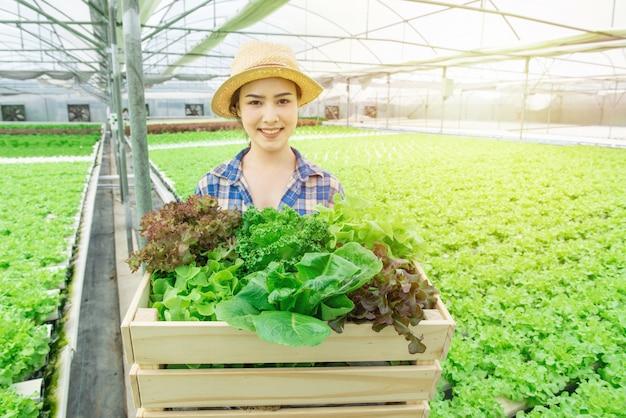 Portret van jonge aantrekkelijke mooie aziatische vrouw oogsten verse groentesalade van haar hydrocultuur boerderij in kas hand houden houten mand en glimlach, small business ondernemer concept Premium Foto