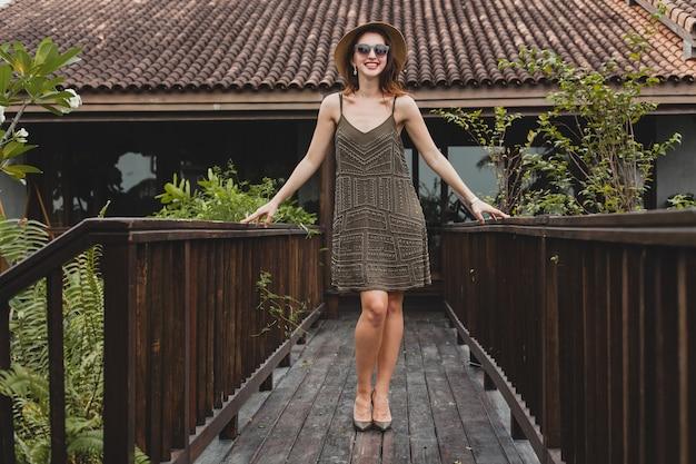 Portret van jonge aantrekkelijke vrouw in elegante jurk, strooien hoed, zomerstijl, modetrend, vakantie, glimlachen, stijlvolle accessoires, zonnebril, poseren op tropische villa op bali Gratis Foto