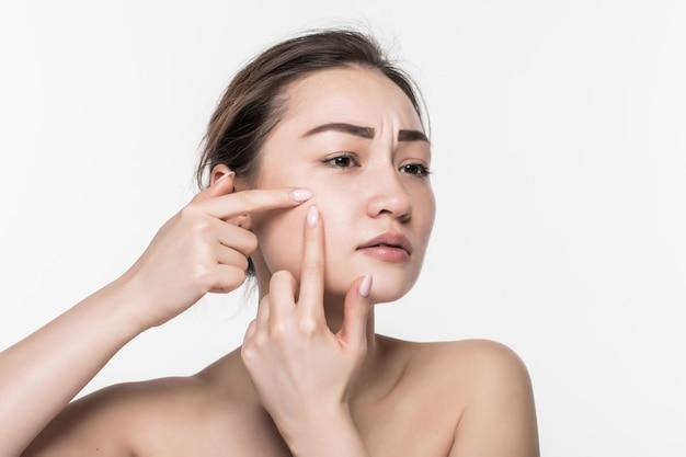 Portret van jonge aantrekkelijke vrouw wat betreft haar gezicht en het zoeken naar acne die op witte muur wordt geïsoleerd Gratis Foto