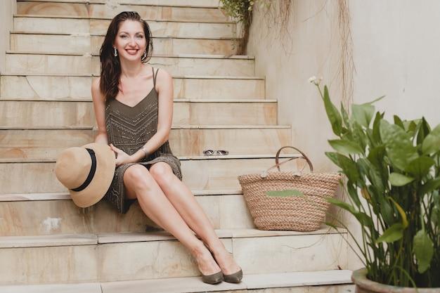 Portret van jonge aantrekkelijke vrouw zittend op de trap in elegante jurk met strooien hoed, zomerstijl, modetrend, vakantie, glimlachen, slanke benen, stijlvolle accessoires, tas Gratis Foto