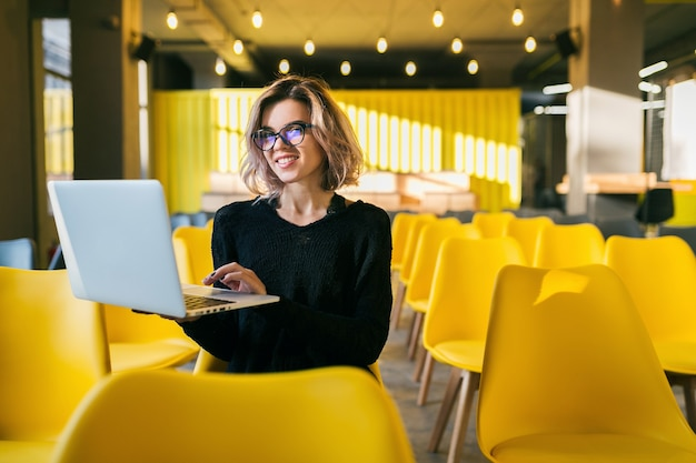 Portret van jonge aantrekkelijke vrouwenzitting in collegezaal die aan laptop werkt die glazen draagt, student die in klaslokaal met veel gele stoelen leert Gratis Foto