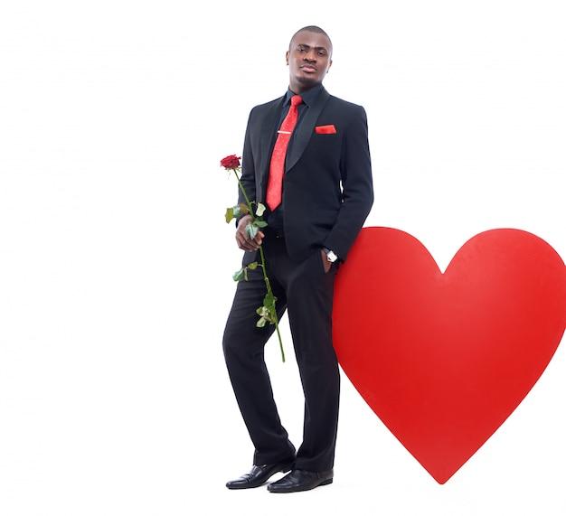 Portret van jonge afrikaanse man in zwarte suite en rode stropdas leunend op grote versierde rood hart Gratis Foto