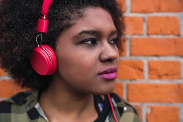 Portret van jonge afro-amerikaanse latijns-vrouw, luisteren naar muziek met een koptelefoon in de straat. buitenshuis. Gratis Foto