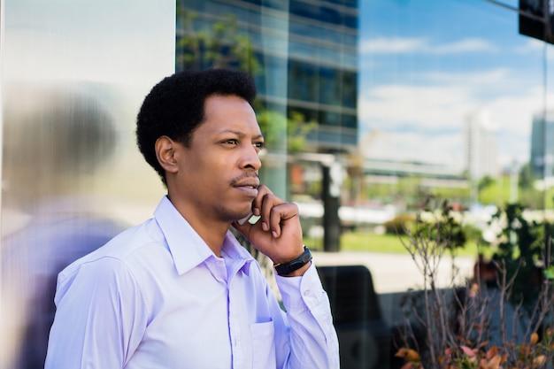 Portret van jonge afrozakenman die op mobiele telefoon buiten op straat spreken. bedrijfsconcept. Gratis Foto