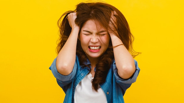 Portret van jonge aziatische dame met negatieve expressie, opgewonden schreeuwen, emotionele boos huilen in casual kleding en kijken naar de camera over gele muur. gelaatsuitdrukking concept. Gratis Foto