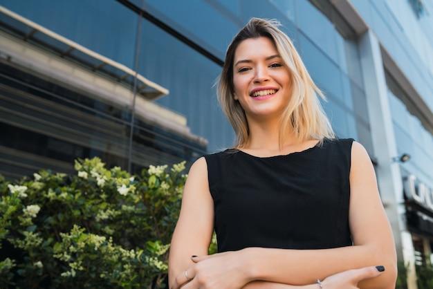 Portret van jonge bedrijfsvrouw die zich buiten bureaugebouwen bevindt. bedrijfs- en succesconcept. Gratis Foto