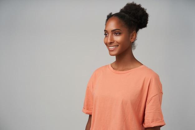 Portret van jonge blije donkerbruine vrouw die positief vooruit kijkt met charmante glimlach terwijl zij op grijs met handen naar beneden staat Gratis Foto