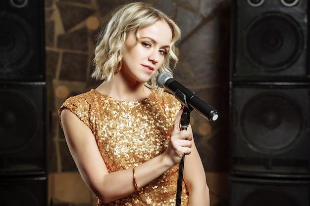 Portret van jonge blondevrouw met microfoon op dark Premium Foto