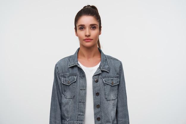 Portret van jonge brunette dame draagt in wit t-shirt en denim jacks, kijkt naar de camera met rustige uitdrukking, staat op witte achtergrond. Gratis Foto