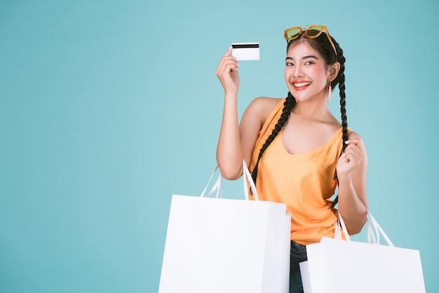 Portret van jonge brunette vrouw met creditcard en boodschappentassen Premium Foto