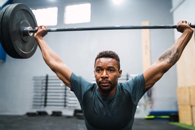 Portret van jonge crossfit-atleet die oefening met een barbell doet. crossfit, sport en gezonde levensstijl. Gratis Foto