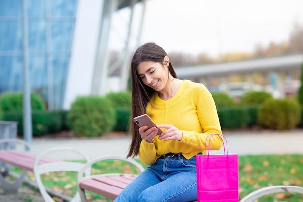 Portret van jonge donkerbruine vrouwenzitting openlucht op bank met het winkelen zakken en het gebruiken van mobiele telefoon. Premium Foto