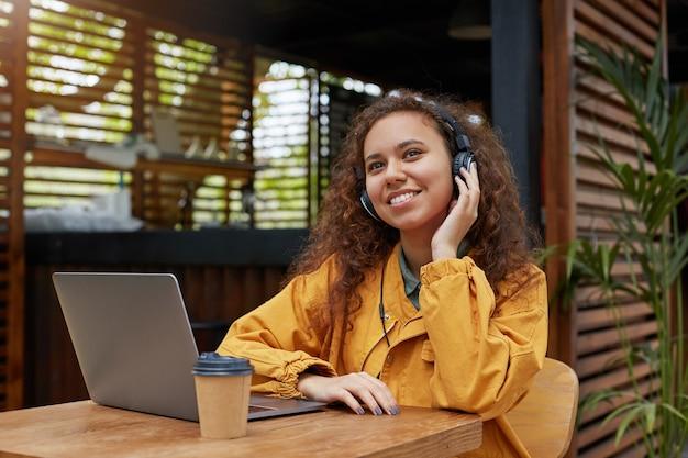 Portret van jonge donkere krullend student meisje luistert naar muziek en droomt van weekendfeest, zittend op een caféterras, gekleed in een gele jas, koffie drinken, werkt op een laptop. Gratis Foto