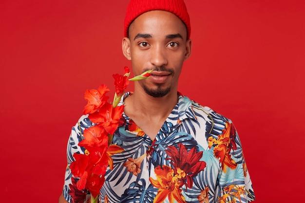 Portret van jonge donkere man, draagt in hawaiiaans overhemd en rode hoed, kijkt naar de camera met kalme uitdrukking, met een rode bloem, staat op rode achtergrond. Gratis Foto