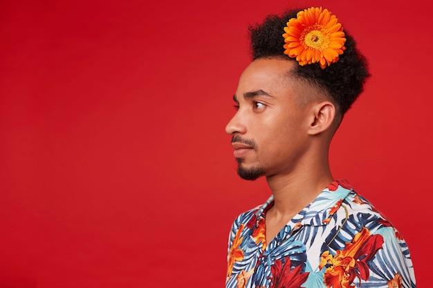 Portret van jonge donkere man, draagt in hawaiiaans overhemd, kijkt weg met kalme uitdrukking, met een oranje bloem in het haar, staat over rode achtergrond. Gratis Foto