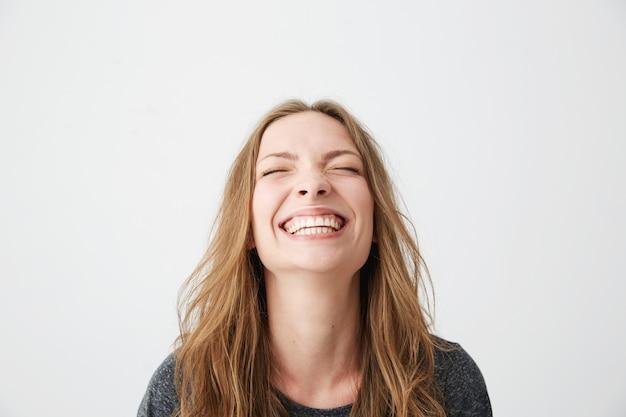 Portret van jonge emotionele mooi meisje lachen met gesloten ogen. Gratis Foto