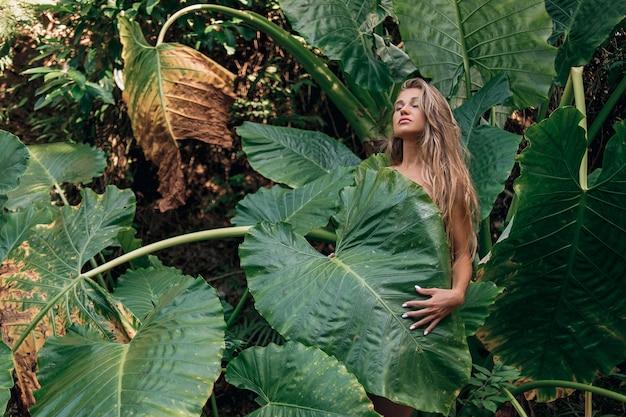 Portret van jonge en mooie vrouw met perfecte gladde huid en lang haar in tropische bladeren. van natuurlijke cosmetica en huidverzorging. - Premium Foto