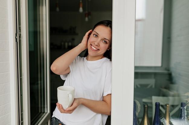 Portret van jonge europese vrouw met donker haar en een gezonde huid lachend met koffie in de ochtend in de moderne lichte keuken. Gratis Foto