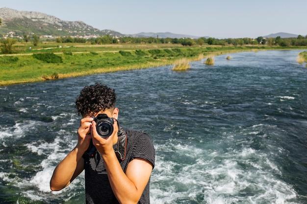 Portret van jonge fotograaf die foto voor camera neemt Gratis Foto