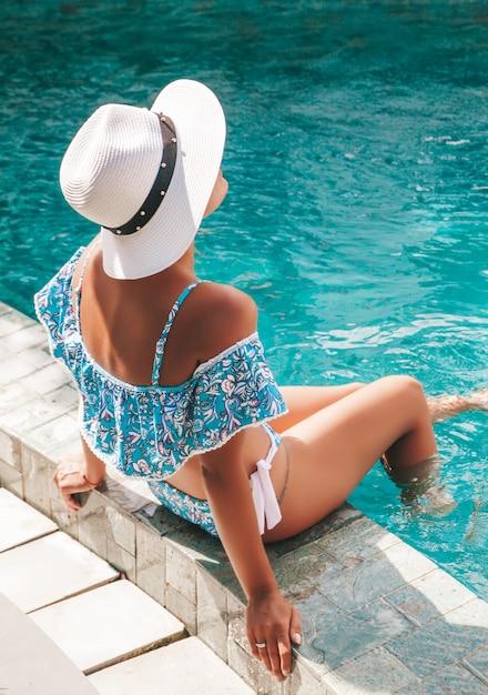 Portret van jonge gebruinde vrouw in blauwe badmode. meisje ontspannen op de rand van het zwembad in de spa resort. model zitten in witte hoed Gratis Foto