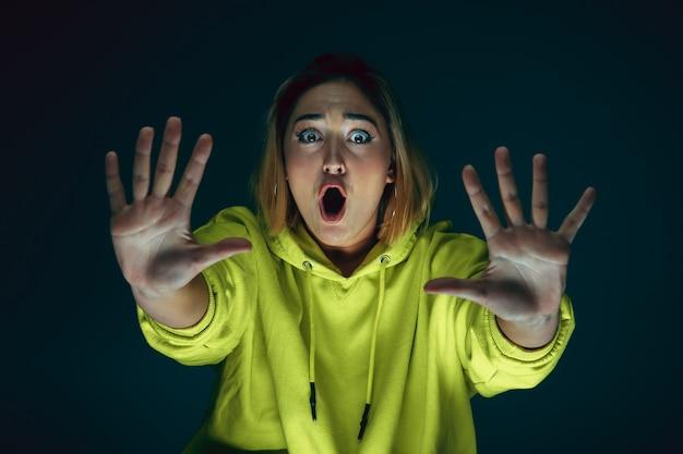 Portret van jonge gekke bang en geschokt blanke vrouw geïsoleerd op donkere achtergrond close-up. Gratis Foto