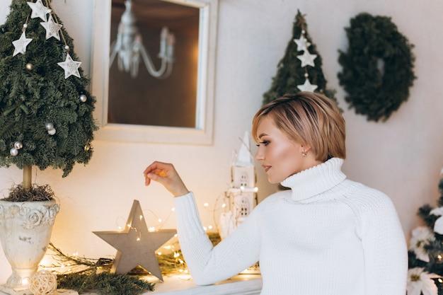 Portret van jonge gelukkige vrolijke vrouw in kerstmis verfraaid huis. kerstmis, geluk, schoonheid, presenteert concept Premium Foto