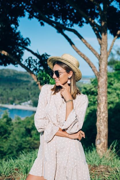 Portret van jonge gelukkige vrouw in zomerjurk, zonnebril en strooien hoed Gratis Foto