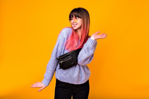 Portret van jonge gelukkige vrouw, positieve opgewonden emoties, felle trendy fuchsia haren, gezellige trui, broek en heuptasje. Gratis Foto
