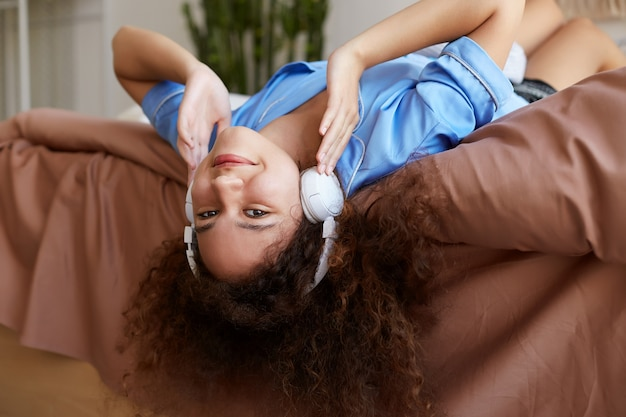 Portret van jonge genieten van krullend mulat meisje liggend op het bed met haar hoofd naar beneden, favoriete muziek in koptelefoon luisteren, glimlachen en ziet er gelukkig uit. Gratis Foto