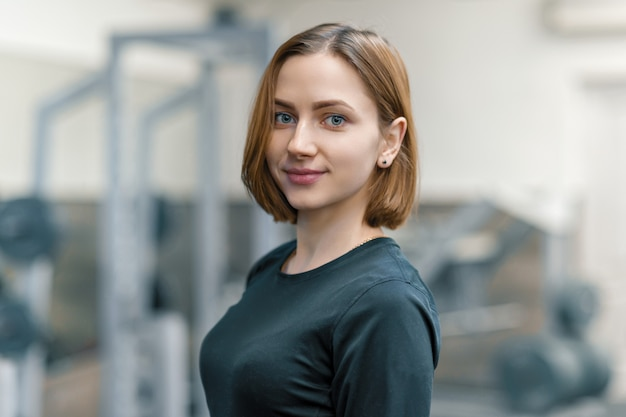 Portret van jonge glimlachende vrouw in de gymnastiek Premium Foto