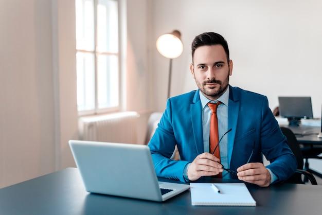 Portret van jonge glimlachende zakenman met laptopzitting in modern bureau. Premium Foto