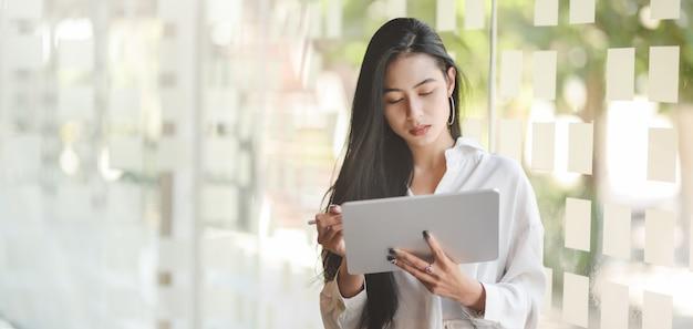 Portret van jonge hartstochtelijke aziatische onderneemster die digitale tablet gebruiken terwijl status in modern bureau Premium Foto