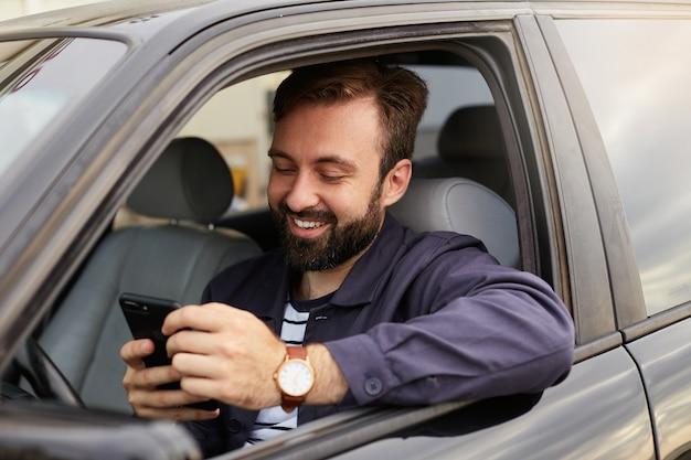 Portret van jonge hendsome succesvolle bebaarde man in een blauwe jas en gestreept t-shirt, zit achter het stuur van de auto, chatten met collega via de telefoon Gratis Foto