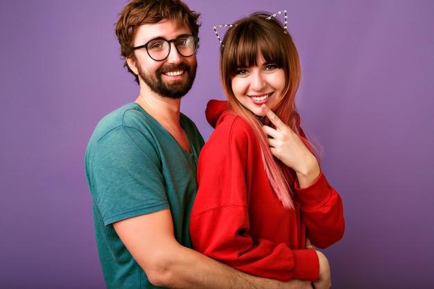 Portret van jonge hipster mooie familie paar knuffels, trendy casual outfits, vriendjes en vriendinnen, relatiedoelen, violette muur dragen Gratis Foto