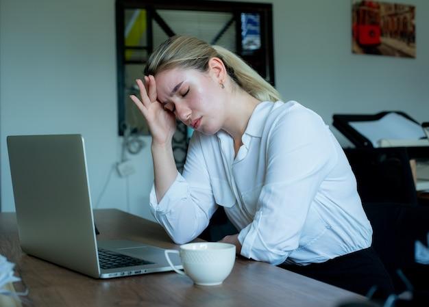 Portret van jonge kantoormedewerker vrouw zittend aan een bureau met behulp van laptopcomputer op zoek onwel aanraken van hoofd lijden aan hoofdpijn werken in kantoor Gratis Foto
