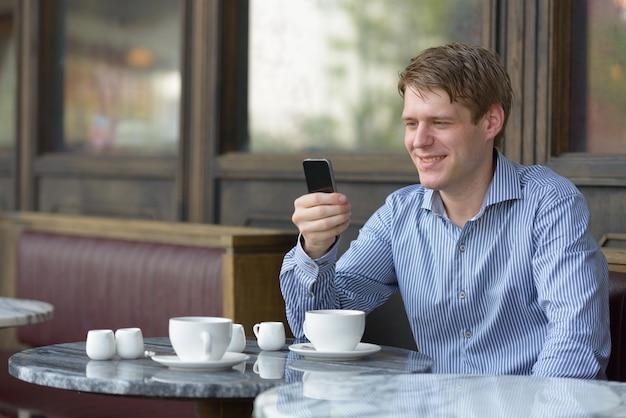 Portret van jonge knappe blonde zakenman ontspannen in de coffeeshop buitenshuis Premium Foto