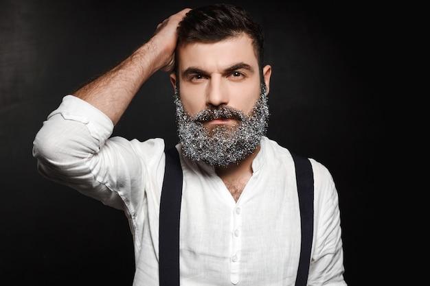 Portret van jonge knappe man met baard in sneeuw over zwart. Gratis Foto