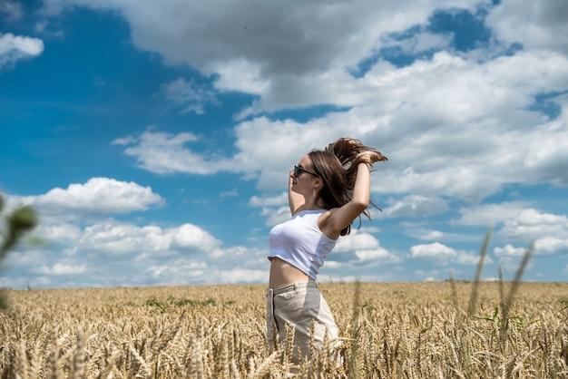 Portret van jonge lachende vrouw in een tarweveld. gratis gelukkig meisje Premium Foto